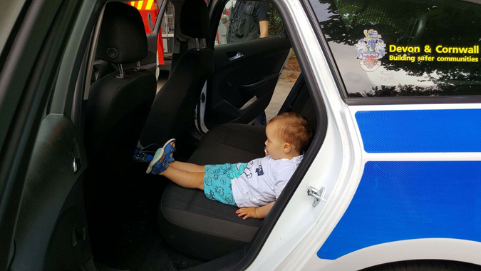 jenson in the back of a police car